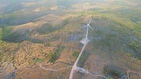 Fliegen über zwei elegante weiße Windkraftanlagen auf grünen Hügeln stock video
