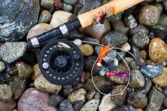 Fliegen-Angelrute und Spule mit Fliegen auf nassen Steinen lizenzfreies stockfoto
