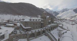 Fliegen auf ein Brummen über einem Kloster in den Bergen im Winter stock video footage
