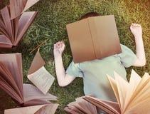Fliegen-Bücher um schlafenden Jungen im Gras Stockfoto