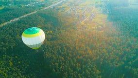Fliegen ?ber den Hei?luftballon Hei?luftballon im Himmel ?ber einem Feld in der Landschaft Schattenbild des kauernden Gesch?ftsma stock footage