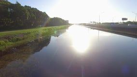 Fliegen über einen Fluss in Richtung zur Sonne stock footage