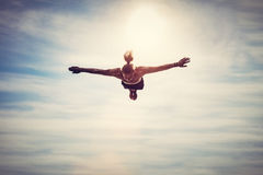 Fliegen des jungen Mannes im Himmel stockbild