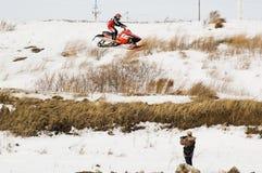 Fliegen des Sportlers auf Schneemobil fahrung und des Pressemannes stockfotos
