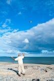 Fliegen eines Drachens auf dem Strand stockfoto