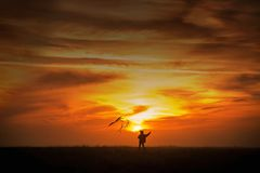 Fliegen eines Drachens Der Junge l?uft ?ber das Feld mit einem Drachen Schattenbild eines Kindes gegen den Himmel Heller Sonnenun lizenzfreie stockfotografie
