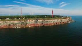 Fliegen entlang die Küste mit Blick auf die Küstenlinie mit Klippen vom Meer und auf Land der alte Leuchtturm und die Windkraftan stock video footage