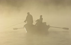 Fliegen-Fischen in einem Antriebboot im Nebel lizenzfreie stockbilder