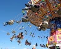 Fliegen Sie in den Himmel - kleines buntes Karussell. Stockfotografie