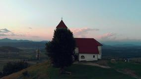 Fliegen um die alte katholische Kirche auf einem Hügel mit einer schönen Ansicht des Dorfs in der Sommerzeit im Sonnenuntergang stock video
