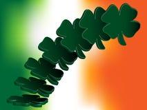 Fliegen von vier Blatt-Klee über irischer Flagge Stockfotografie