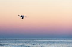 Fliegenbrummen mit Kamera auf dem Himmel bei Sonnenuntergang Stockfotografie