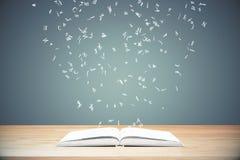 Fliegenbuchstaben vom geöffneten Buch auf Holztisch Stockfoto