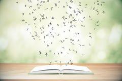 Fliegenbuchstaben vom geöffneten Buch auf Holztisch Lizenzfreie Stockbilder