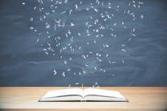Fliegenbuchstaben vom geöffneten Buch auf Holztisch an der Tafel Lizenzfreie Stockbilder