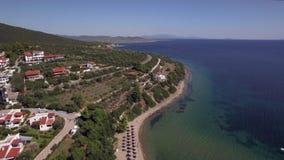 Fliegend über Meer, setzen Häuschen und Erholungsort auf der Küste Trikorfo, Griechenland auf den Strand stock video