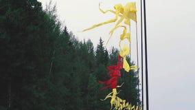 Fliegende bunte Fahnen auf Fahnenmasten gegen den Hintergrund des Kiefernwaldes während des Sommerfestivals stock footage