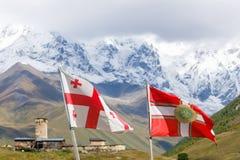Fliegende Flagge von Georgia und Flagge der georgischen Grenzpolizei Mit Svans Turm und Bergen auf dem Hintergrund, Svaneti lizenzfreie stockfotos