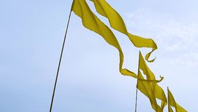 Fliegende gelbe Fahnen auf Fahnenmasten auf Himmelhintergrund während eines Ereignisses im Freien stock video footage