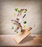 Fliegende rohe ganze Forelle fischt mit Gemüse, Öl und würzt Bestandteile über hölzernem Schneidebrett für das geschmackvolle Koc Lizenzfreie Stockfotos