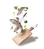 Fliegende rohe ganze Forellenfische mit Gemüse, Öl und Gewürzbestandteilen über hölzernem Schneidebrett für das geschmackvolle Ko Stockfotografie