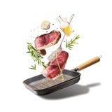 Fliegende rohe Rindfleischsteaks, mit Kräutern, Öl und Gewürzen mit der Grillwanne und Küchengeräten, lokalisiert auf weißem Hint Lizenzfreie Stockfotos