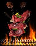 Fliegende rohe Steaks mit Bestandteilen, Lebensmittelzubereitungskonzept Lizenzfreies Stockfoto
