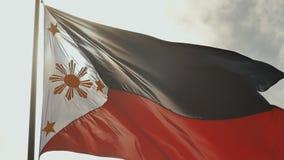 Fliegende zweifarbige Flagge der Philippinen mit der zentralen goldenen Sonne, welche die Provinzen und die Sterne die Inseln dar stock video