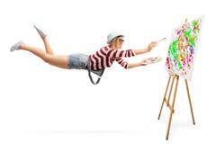 Fliegender weiblicher Maler, der eine Malerei zeichnet Stockfotografie