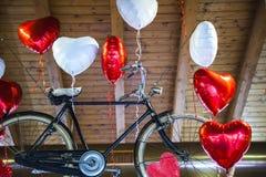 Fliegendes altes Fahrrad springen zu Herz geformten Ballonen Stockfotografie