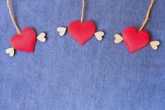 Fliegendes Herz auf blauem Baumwollstoffhintergrund Liefern des Liebesrahmens Hintergrund für Valentine' s-Konzept stockfoto