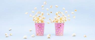 Fliegendes Popcorn in einem hellen Glas und auf einem blauen Hintergrund Kopieren Sie Platz stockfoto