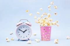 Fliegendes Popcorn in einem hellen Glas und in einem Wecker auf einem blauen Hintergrund stockbilder