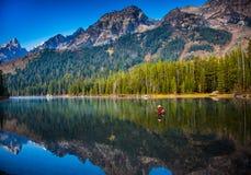 Fliegenfischer wirft im See in großartigem Nationalpark Teton lizenzfreies stockfoto