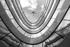 Fliegenflugzeug und modernes Architekturgebäude Lizenzfreie Stockfotos