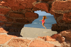 Fliegenfrauenansicht durch Loch in den Felsen Stockfotos