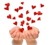 Fliegenherzen von schalenförmigen Händen der jungen Frau, Valentinstag, Glückwunschkarte Stockbild