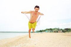 Fliegenkerl, der Spaß auf dem Strand hat und eine gute Zeit hat Stockfotografie