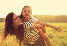Fliegenkindermädchen, das auf der glücklichen genießenden Mutterrückseite auf SU lacht Stockfotografie