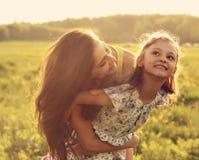 Fliegenkindermädchen, das mit glücklicher genießender Mutter auf Sonnenuntergangbr lacht Lizenzfreies Stockfoto