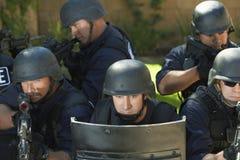 Fliegenklatsche-Offiziere, die mit Gewehr hinter Schild zielen stockfotos