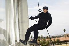 FLIEGENKLATSCHE Team Officer Rappelling And Aiming-Gewehr Lizenzfreie Stockbilder