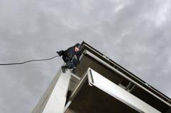 FLIEGENKLATSCHE Team Officer Rappelling und zielen Gewehr Lizenzfreie Stockfotografie