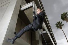 FLIEGENKLATSCHE Team Officer Rappelling und zielen Gewehr Lizenzfreie Stockbilder