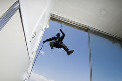 FLIEGENKLATSCHE Team Officer Rappelling vom Gebäude Stockfotos