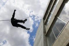 FLIEGENKLATSCHE Team Officer Rappelling vom Gebäude Stockbilder