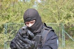 Fliegenklatschepolizeibeamte, der ein Gewehr auf die Kamera zeigt Stockfotos