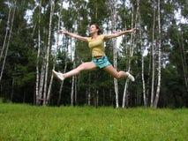 Fliegenläufermädchen unter Gras Stockfoto