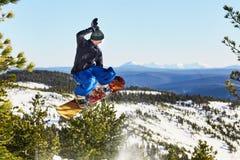 Fliegensnowboarder in den Bergen Lizenzfreie Stockfotografie