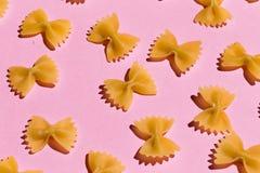 Fliegenteigwaren lokalisiert auf rosa Hintergrund lizenzfreie stockfotografie